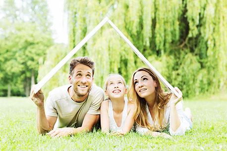 Ein junges Paar, mit einem Mädchen in der Mitte, welche auf einer Wiese liegen und ein Dach über sich halten